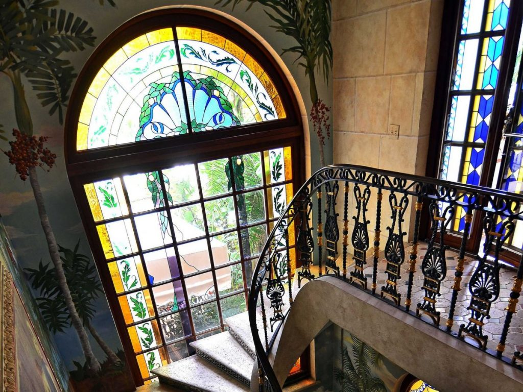 there-are-plenty-of-opulent-details-throughout-the-home-like-these-stained-glass-windows-wall-frescoes-and-intricate-staircase-railing